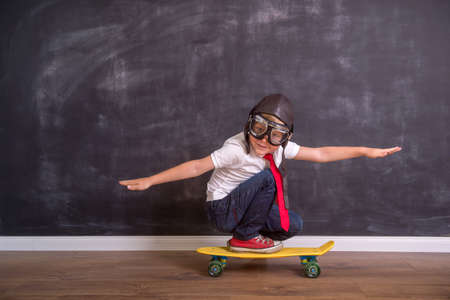 Kid with pilot helmet. Child playing at home. Success, imagination and innovation technology concept