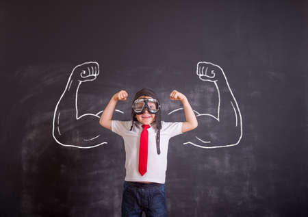 Portrait of kid in pilot helmet. Success, creative and start up concept. Child showing muscles against blackboard. Copy space for your text