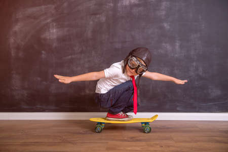 Kid with pilot helmet. Child playing at home. Success, imagination and innovation technology concept. Back to school