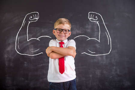 Child with confidence ready to defense from bullying. School boy in uniform and glasses. Kid showing bicep muscles with muscles drawn on chalkboard. Back to school