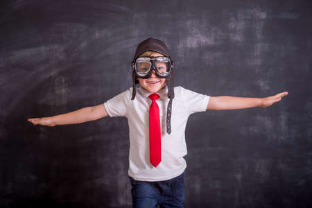Kid dream to be a pilot. Back to school. Portrait of young businessman make wings. Success, creative and start up concept. Copy space for your text