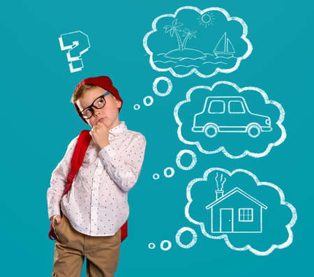 Little boy making choice isolated on blue. Kid dreaming about his future - traveling, car and house