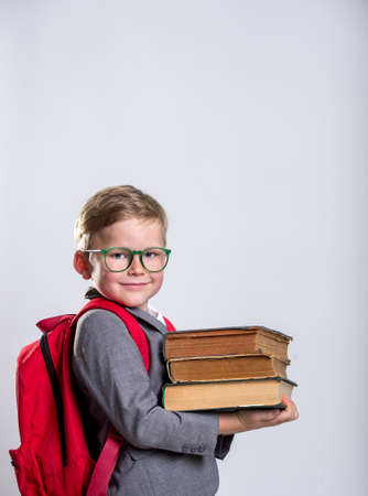 Happy schoolboy with backpack and books isolated on white background. Back to school concept.