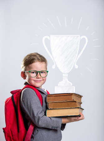 Portrait of child with stack of books and win cup. Kid with books in class. Success, idea and win concept. Back to school. Smart pupil in glasses Reklamní fotografie