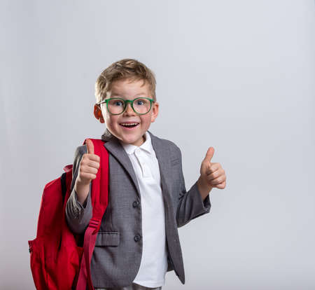 Back to school. Happy smiling kid boy with red backpack and having fun against blue wall. Looking at camera. School concept. Reklamní fotografie