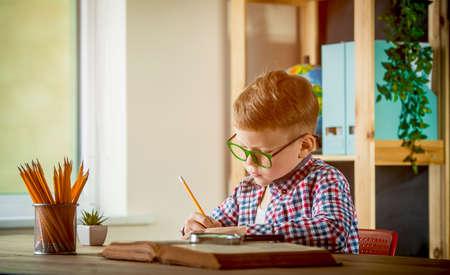 Little boy writing on blank paper. Smart kid sitting on a desk near the window. Back to school Reklamní fotografie