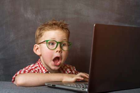 Shocked kid and laptop. Back to school. Online education. Protect kids from internet