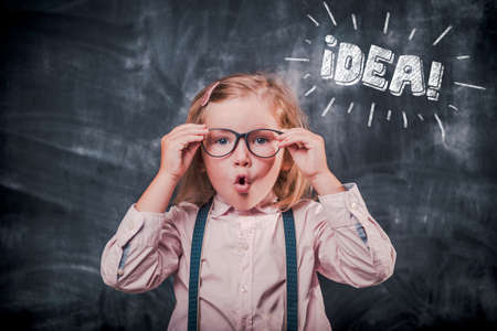 School kid in class. Happy child in glasses has idea. Education concept
