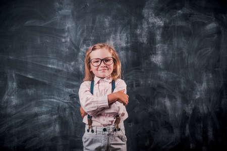 Smart little kid ready to go to school. Kid in glasses against blackboard.