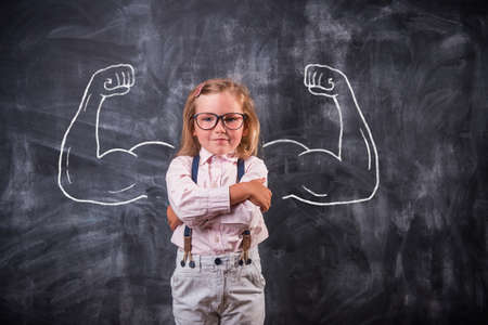 Funny school child showing muscles. Big and strong bicep concept for strength, confidence or defense from bullying Reklamní fotografie