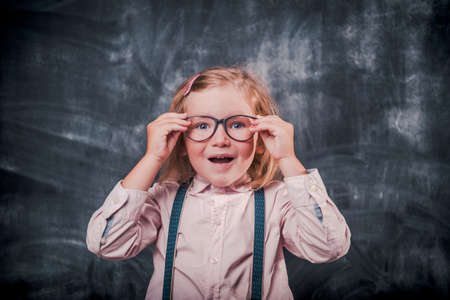 Smart little kid in glasses against blackboard. Genius back to school