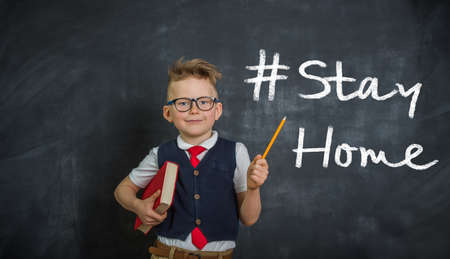 Stay at home. Child during coronavirus with pencil pointing up on banner Stay at home. Back to school.