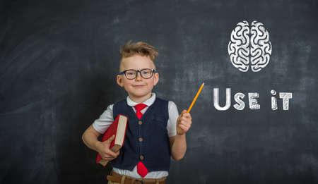 Portrait of child pointing on brain. Genius. Back to school.