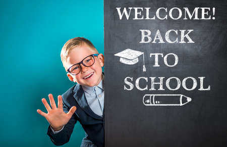 Happy smiling child with blackboard blank. Back to school concept. Little genius in glasses wave hello. Welcome Reklamní fotografie