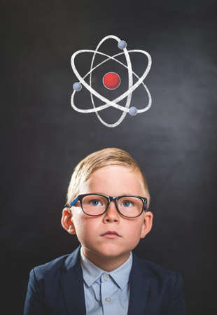 Kid and atom against blackboard. Explore this great world. Back to school.