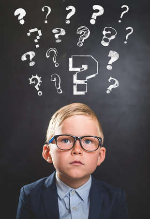 Funny school child with many question marks on blackboard. Little genius