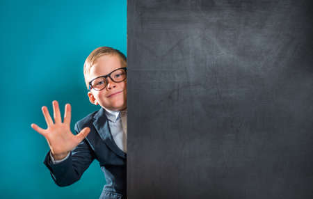 little kid showing 5 fingers. Pupil of primary school with blank blackboard for your text. Go back to school. Poster