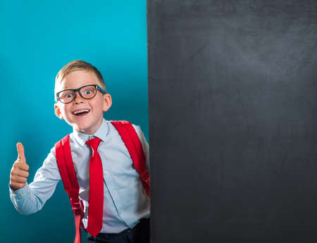 Portrait of smart school child with thumb up near blackboard blank and looking at camera. Happy kid boy in uniform. Go back to school. First day of fall.