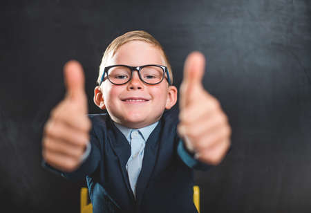 Portrait of smart school child with thumb up near blackboard blank and looking at camera. Happy kid boy in uniform. Go back to school. First day of fall. Boy in glasses Reklamní fotografie
