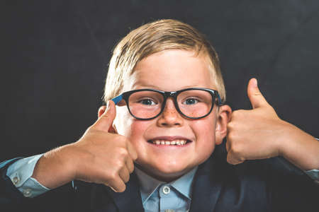 Portrait of smart school child with thumb up near blackboard blank and looking at camera. Happy kid boy in uniform. Go back to school. First day of fall. Funny face