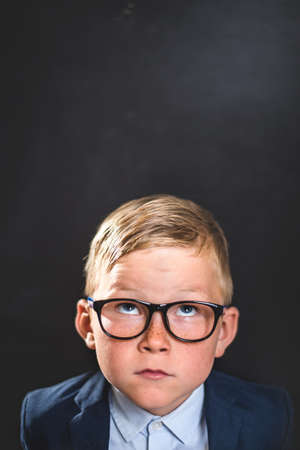 Thinking child. Portrait of smart school child with thumb up near blackboard blank and looking at camera. Happy kid boy in uniform. Go back to school. First day of fall.