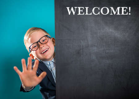 Welcome and hello. Portrait of smart school child with thumb up near blackboard blank and looking at camera. Happy kid boy in uniform. Go back to school. First day of fall.
