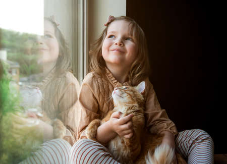 Little child girl read a book near the window. Education and school concept. Kid with book in hands. Fast read. Cat pet