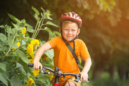 Portrait of a cute boy on bicycle. Happy smiking kid on bike. Child in safety helmet and orange shirt playing outdoors in park. Sport and healthcare concept. School kid in bike. Safety