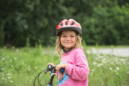 Portrait of funny girl in a pink safety helmet on bike. Beautiful little kid on park.