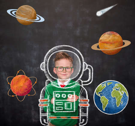 Childhood. Nerd kid boy dreams about future. School boy astronaut in space suit with pictures of space and planets on blackboard. Rocket and win concept Reklamní fotografie