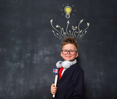 Portrait of a stylish child boy in school business suit wearing glasses. International English school. Kid boy with question marks and a yellow light bulb drawn above his head Reklamní fotografie