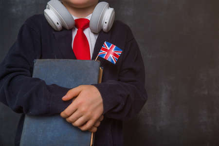 Kid in uniform holding a flag of United Kingdom and book in hands. Great Britain flag. British flag. Education and learn English. International language school concept