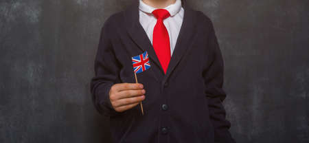 Kid in uniform holding a flag of United Kingdom and book in hands. Great Britain flag. British flag. Education and learn English. International language school concept. Blackboard