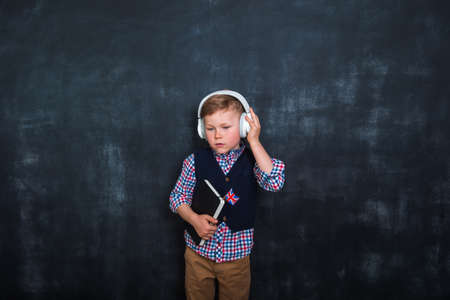 Kid in uniform and headphones holding a flag of United Kingdom and book in hands. Great Britain flag. British flag. Education and learn English. International language school concept. Innovation