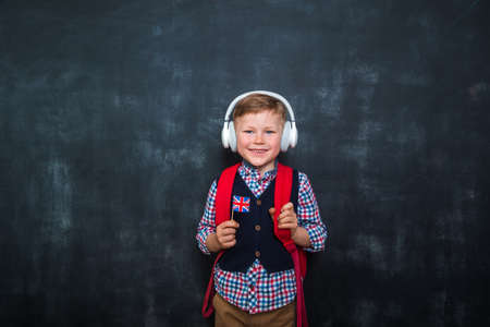 Kid in uniform and headphones holding a flag of United Kingdom and book in hands. Great Britain flag. British flag. Education and learn English. International language school concept. Reklamní fotografie