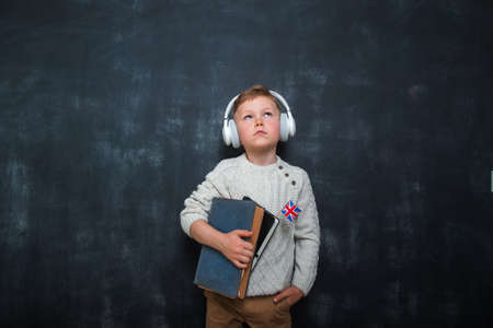 Kid in uniform and headphones holding a flag of United Kingdom and book in hands. Great Britain flag. British flag. Education and learn English. International language school concept. Leader