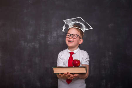 Smart educated school kid student with graduation hat doodle picture on chalkboard. little boy with paintbrush creative drawing light bulb ideas on wall.