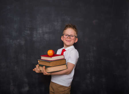 Adorable child whit books and apple in hands. Back to school. Education. Blackboard on background. Kid pupil boy in uniform.