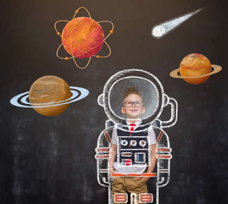 Childhood. Nerd kid boy dreams about future. School boy astronaut in space suit with pictures of space and planets on blackboard. Rocket and win concept. Innovation