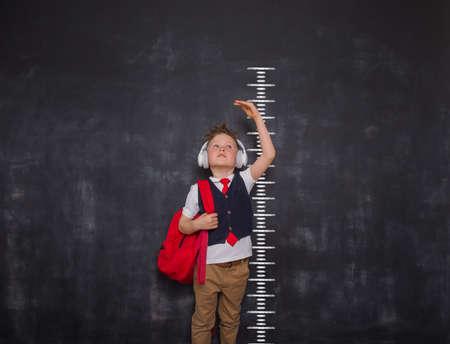 Little kid boy measuring himself. School boy measuring his growth in height against a blackboard scale. Back to school