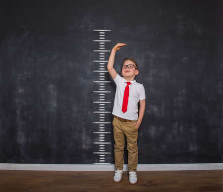 Little kid boy measuring himself. School boy measuring his growth in height against a blackboard scale. Back to school. Ready to go to school