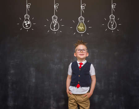 Portrait of school child businessman thinking about solution. Bright idea. Innovation. Kid with eyes looking up on bulb drawing on blackboard. Success growing business concept