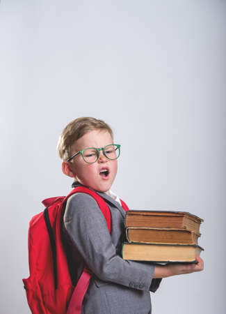 Back to school. Child with a backpack holding heavy school books