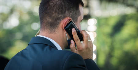 Security officer use radio.. bodyguard standing and listening message with security earpiece on helipad. Security guard man on event. Secret service. Private guard in crowd, Phone