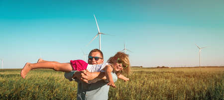 Little girl in fathers hands in front of windmills. Funny kid flying. Renewable energies and sustainable resources. child playing with dad near a wind turbine.