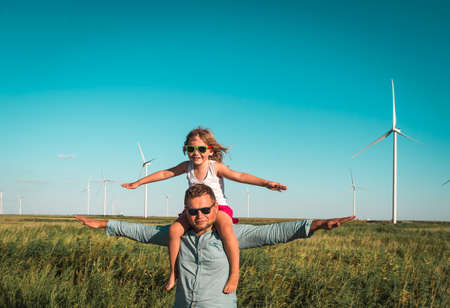 Family father and little kid near wind turbines. go for a walk between wind turbines. concept of ecology and alternative energy