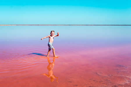 Funny little kid boy running in pink salt lake on a sunny summer day. Exploring nature, travel, family vacation in Kherson region, Ukraine. Happy time for child