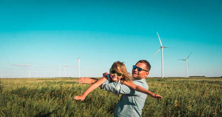 Family father and little kid near wind turbines. go for a walk between wind turbines. concept of ecology and alternative energy. Future of Windmills