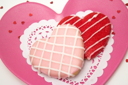 Heart cookies with icing on pink plate with white doily Stock fotó