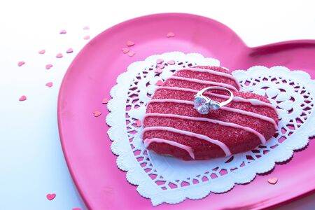 Sugar cookie with engagement ring on pink plate with white doily